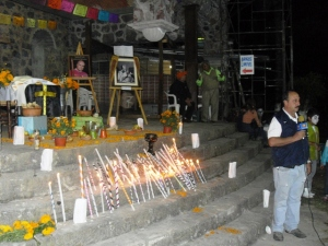 Periodista de Televisa reporta ante la ofrenda dedicada al obispo Don Sergio Méndez Arceo, conocido por ser de los primeros teólogos de la Liberación en México.