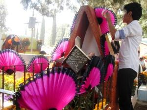 El nieto decora con abanicos la tumba de su abuela, quien gustaba de ellos.